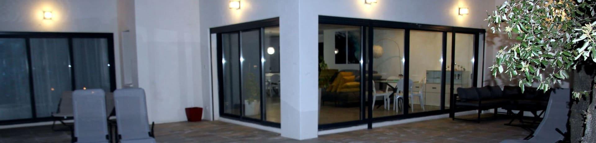 Façade vitrée de la villa tout confort ouvrant sur la terrasse avec bains de soleil et piscine privatisée